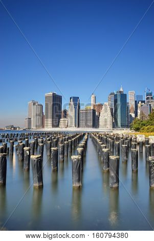 Old pier pylons and Downtown Manhattan New York City.