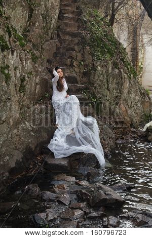 Young woman with blue eyes dressed bride sitting on a stone stairs in the countryside near a river.