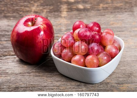 Grapes in bowl and apple on the wooden table in natural light