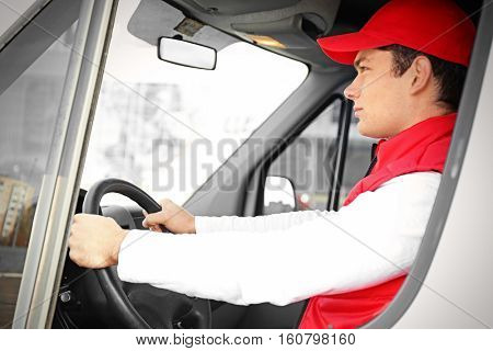 Young male courier driving delivery service van