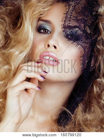 Portrait of beauty blond glamorous young woman through black lace close up