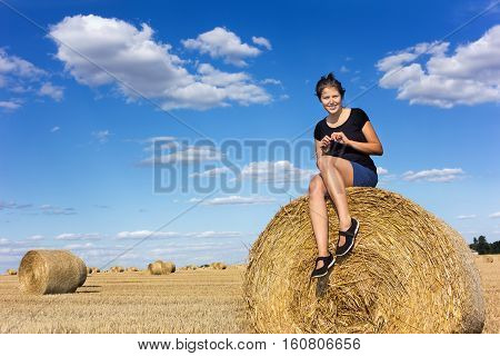Rural girl on straw bale in a field