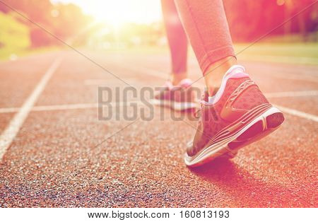 fitness, sport, training, people and lifestyle concept - close up of woman feet running on track from back