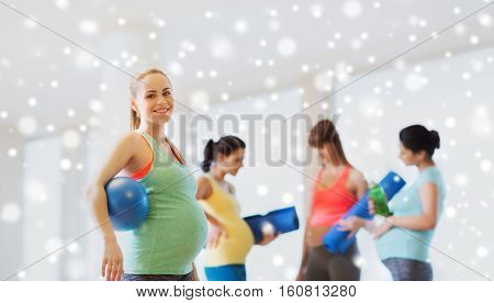 pregnancy, sport, fitness, people and healthy lifestyle concept - happy pregnant woman with ball in gym over snow