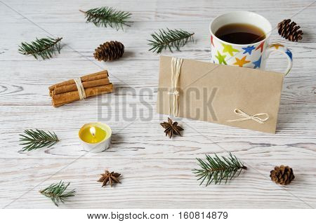Cup of coffee with spices and burning candle on white wooden background. Christmas concept. Envelope for copyspace