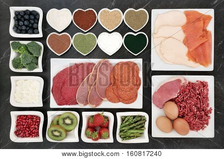 Large body building health food selection with meat, fish, supplement powders, dairy, fruit and vegetables on porcelain plates.