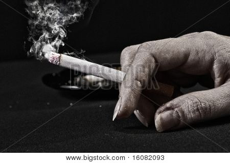 Old woman hand holding a cigarette with smoke