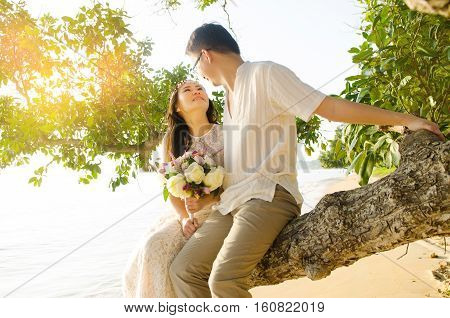 Outdoor Bride and groom on the beach with sunset in the evening.