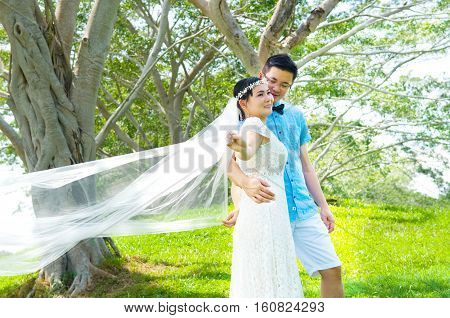The asian couple embracing in the park