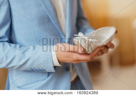 the groom in a blue dress holding wedding shoe bride