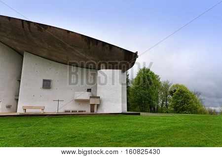 RONCHAMP, FRANCE - APRIL 23, 2016: Pilgrimage Church of Notre Dame du Haut in Ronchamp in the Vosges mountains. Detail of the facade on the background of mountain scenery. The architect is Le Corbusier. Franche-Comte, France.