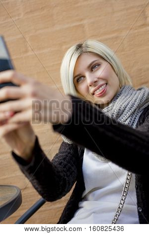 Young woman making faces while taking selfie from smart phone at outdoor cafe