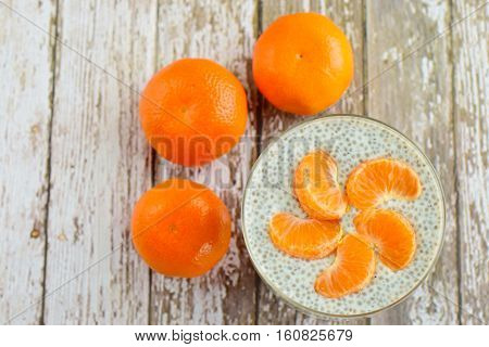 Chia seed milk pudding with clementine on white wooden background