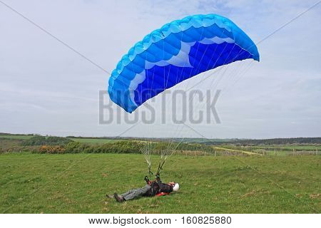 paraglider ground handling his wing lying on the ground