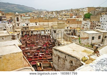 FEZ MOROCCO - MAY 19 2006: City skyline and view of rooftops and workers in the dye pots at leather tanneries at the Terrace de Tanneurs in the ancient medina Fes el Bali in Fez Morocco.