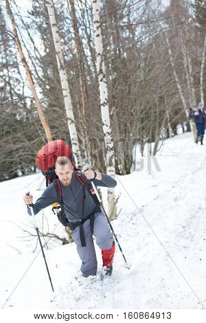 Guy tourist makes the ascent to the mountain in deep snow