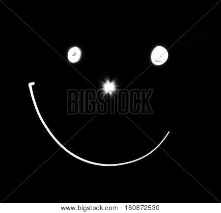 Smiley face. White smile poster. World smile day. Funny white smiley and black background. Photo long exposure and a flashlight