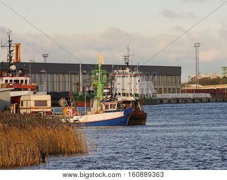 Caravan trailer parked in port, near fishing boat. Industrial landscape