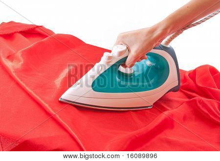 Electric iron on red cloth isolated on white