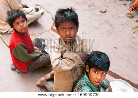 MADHYA PRADESH, INDIA - DEC 30, 2012: Unidentified poor children play on the street on December 30, 2012 in Chitrakoot India. Madhya Pradesh is the 2nd largest Indian state with 105592 primary schools