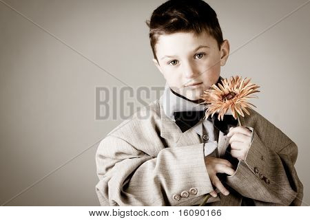 Cute little boy one flower in his hands in sepia
