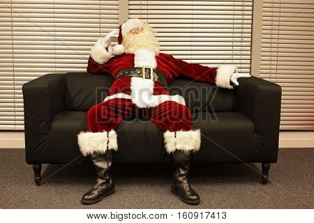 ready santa claus waiting for christmas job sitting on sofa in office