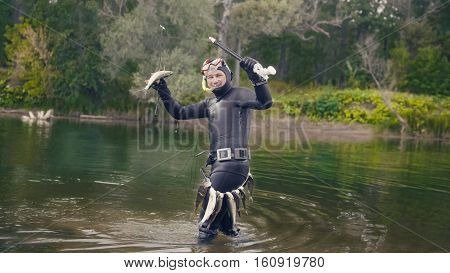 Spear fisherman shows Freshwater Fish at spear of underwater fisherman after hunting in forest river, wide angle
