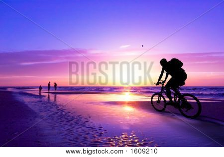 Mountain Biker On Beach And Sunset