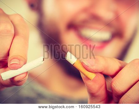 Smilling man breake down cigarette. Winning with addicted nicotine problems stop smoking. Quitting from addiction concept.