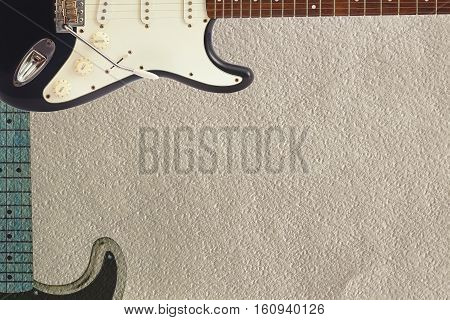 Black and grey electric classic guitars on the rough cardboard background with plenty of copy space.