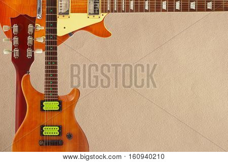 Mahogany and honey sunburst electric guitars and neck on the rough cardboard background with plenty of copy space.