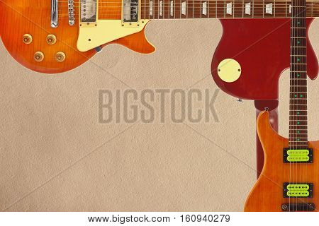 Mahogany and sunburst electric guitars and and back of guitar body on the rough cardboard background with plenty of copy space.