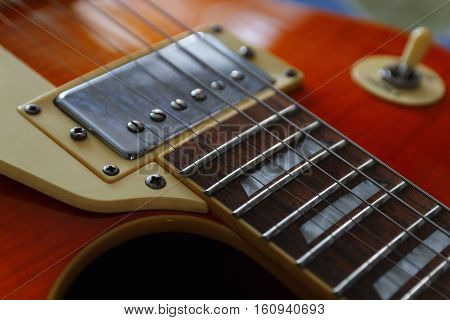 Closeup of the solid body electric guitar. Detail selective focus low key.