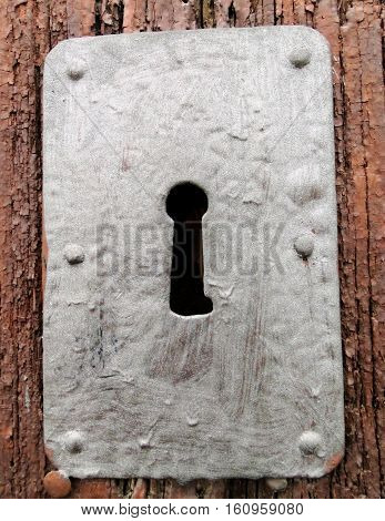 Old fashion keyhole with metal frame on wooden door.
