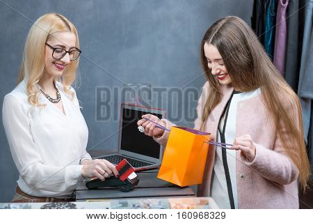 Happy woman buying clothing accessories at the paydesk with cashier making a payment with credit card in the clothing store