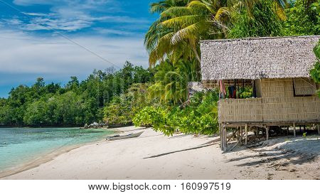 Bamboo Hut under Palm Trees of an Homestay on Gam Island, West Papuan, Raja Ampat, Indonesia.
