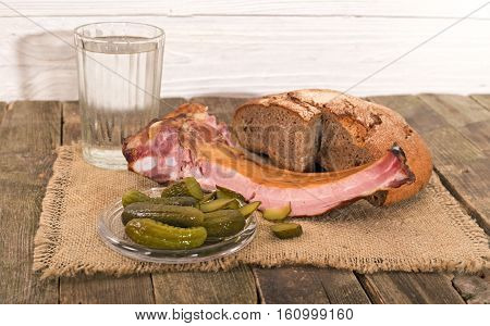 Products on an old wooden table rural style. On napkin from a sacking bread ham on edges pickles and a knife nearby a glass of water lies.