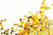 Постер, плакат: Золотые звезды в форме конфетти на белом фоне