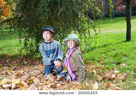 Portrait of Happy girl and boy  enjoying golden autumn fall season