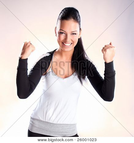 Champion woman standing with fists clenched in victory. Studio shot
