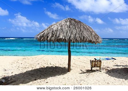 Umbrella and wooden chair on beautiful tropical beach  Maguana, Guantanamo province, Cuba