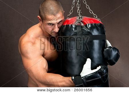 Attractive athletic young man training kickboxing using black punching bag