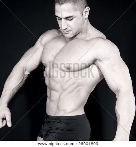 Athletic sexy attractive male body builder, demonstrating contest pose. Studio shot