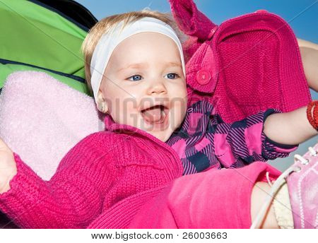 Beautiful happy baby is sitting in buggy and smile under blue sky.