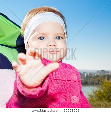 Beautiful happy baby is sitting in buggy and waving under blue sky.