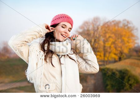 Beautiful happy woman listening music in autumn colored park