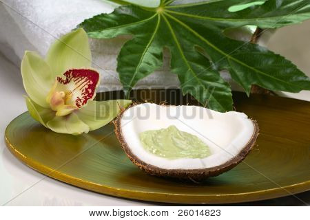 Avocado coconut scrub in coconut shell, orchid flower (Cymbidium sp.), tropical plant and soap. Suited for relaxing and health commercials
