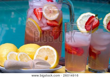 Two glasses of home made iced cold pink strawberry lemonade and pitcher on hot summer on edge of swimming pool.