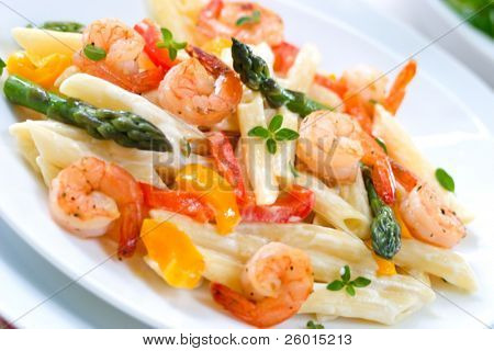 Closeup of plate of Shrimp Penne (tube-shaped pasta) with asparagus, bell pepper, origan and creamy Alfredo sauce . Shallow DOF