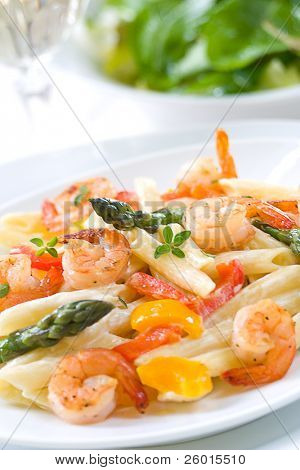 Shrimp Penne (tube-shaped pasta) with asparagus, bell pepper, origan and creamy Alfredo sauce . Green salad. Shallow DOF